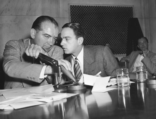 Sen. Joseph McCarthy covers the microphones with his hands while having a whispered discussion with Roy Cohn, his chief counsel, during a committee hearing on April 26, 1954, in Washington. | AP Photo